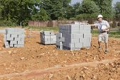 image of cinder block  - Code enforcement officer inspecting cinder blocks for quality - JPG
