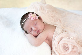 stock photo of newborn baby girl  - A beautiful sleeping newborn baby girl with a peach colored vintage lace scarf and flower headpiece - JPG