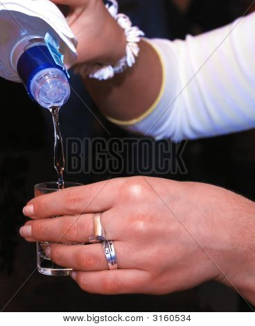 Woman'S Hands Pouring Cold Vodka To The Small Glass