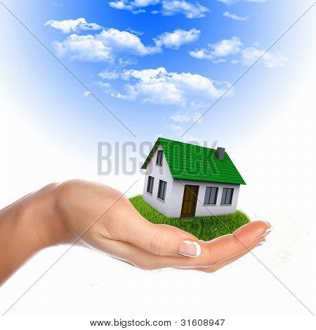 Casa y mano humana contra el cielo azul