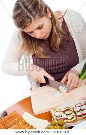 Frau hacken Frühlingszwiebeln und Vorbereitung Brötchen