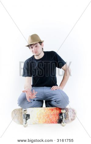 Serious Looking Teenager Sitting On Skate