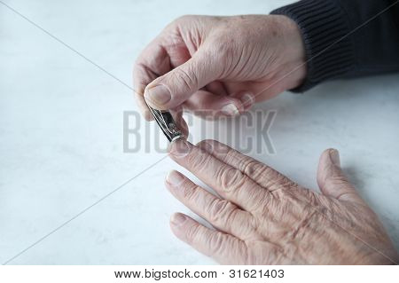 older man trims fingernails