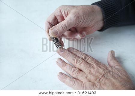 older man trims fingernails
