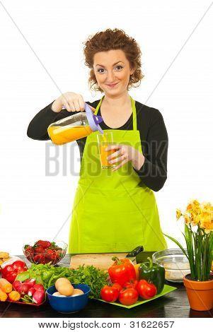 Mulher derramada o suco de laranja em vidro