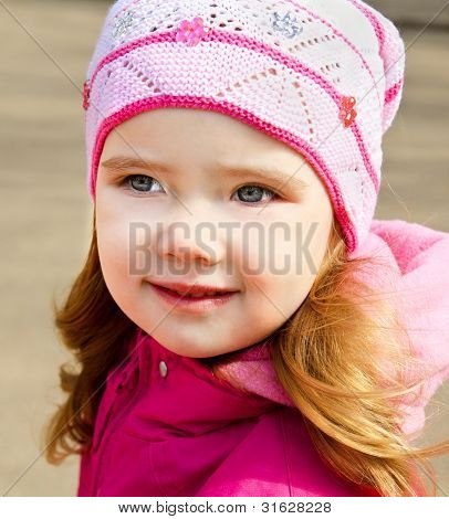 Portrait Of Little Girl Outdoors On A Spring Day