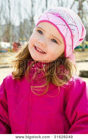 Portrait Of Smiling Little Girl Outdoors On A Spring Day