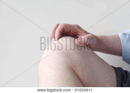man grasps his sore knee