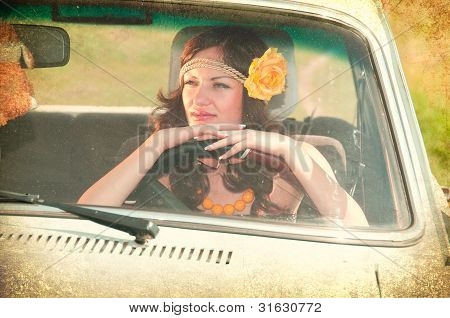 Beautiful Brunette With Flower In Her Hair Sitting Behind The Wheel Of An Old Car. Photos In The Old