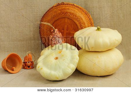 Three Scallop Squashes, Handbells And A Straw Basket On The Linen Cloth