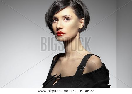 Model Fashion Woman In Black With Bare Shoulders And Red Lips Posing On A White Background