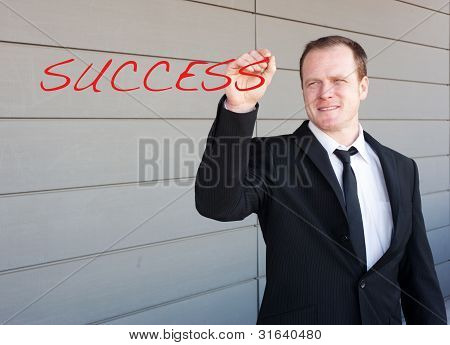 Businessman Writing The Word Success On Screen