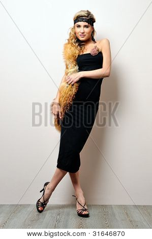 Beautiful Woman In A Black Dress. Studio Portrait.
