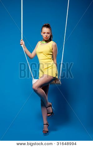 Sexy woman in yellow on swing with bright make-up