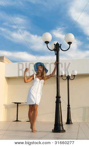 Fashionable Woman With A Wine Glass Standing Beside Street Lamp