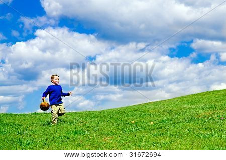Easter egg hunt with young boy running with basket to collect Easter Eggs