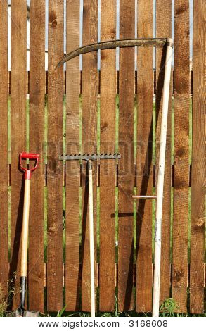Garden Tool Set Over Wood Backyard Fence