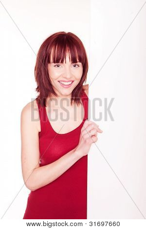 Smiling pretty redhead woman standing alongside a large blank vertical white signboard for your text