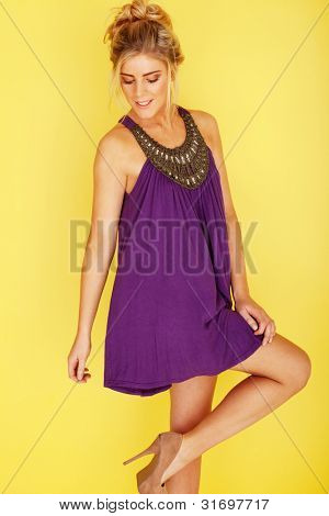 woman in a purple dress looking at her stilleto heels, her right knee slightly bent up, on a yellow background