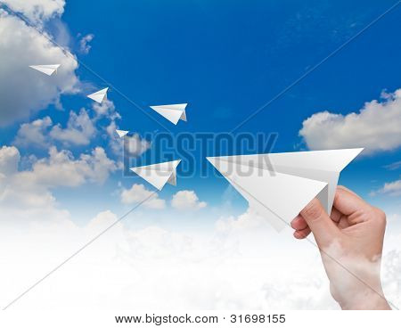 Hand throwing a paper plane in the sky