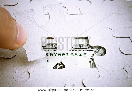 Puzzle in the male hand and hundred-dollar bill under puzzle