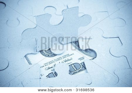 Hundred-dollar bill under the puzzle - blue toned image