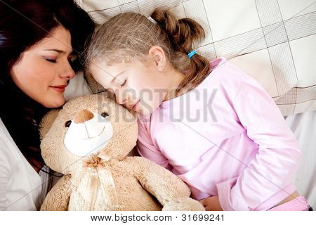 Girls bedtime sleeping with her mother and a teddy bear