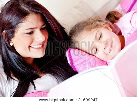 Cute girl reading a bedtime story with her mother
