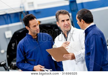 Car mechanics at the auto repair shop talking