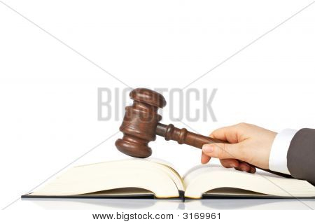 Holding A Wooden Gavel Over The Law Book