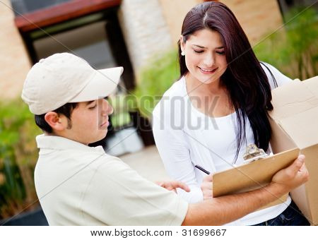 Woman receiving a package at home from a delivery guy