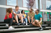Joyful Caucasian Guy Telling Exciting Story To Friends. Interracial Group Of Young People Sitting On poster