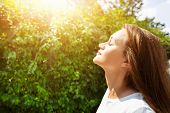 Side View Of Beautiful Young Woman Closing Her Eyes And Breathing Clean Fresh Air poster