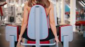 A Woman With Blonde Hair Training In The Gym - Training Her Legs On The Butterfly Training Apparatus poster
