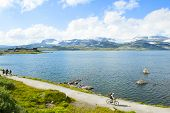 Tourists Hiking And Tourist Biking In Finse, Norway On July 2019 poster