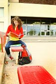 stock photo of bagpack  - young student study book school and bagpack is sit on a red bench - JPG