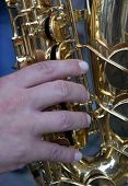 Musical Instrument Saxophone Close-up. Hands On A Musical Instrument. A Musical Instrument Used By A poster