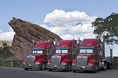stock photo of 18-wheeler  - The beautiful Three 18 Wheeler Red Semi - JPG
