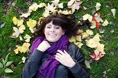 image of teenage girl  - pretty young brunette girl lying in autumn leaves smiling - JPG