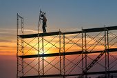 Man Working On Construction Site With Scaffold And Building With Sunset Background,scaffolding For C poster