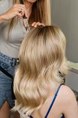 Beautiful Model Girl Blonde With Long Curled Hair. Creating Hairstyle Hollywood Wave. Hairdressing S poster