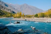 Clear Turquoise Blue Water River Flowing Along Hindu Kush Mountain Range In Ghizer Valley. Autumn Sc poster