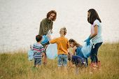 Woman With Group Of Kids Collecting Garbage On A Meadow Next To The River On A Cloudy Summer Day. En poster