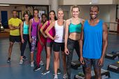 Portrait of diverse fit people standing together in fitness center. Bright modern gym with fit healt poster