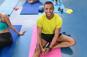 Portrait of African-american fit man relaxing on a exercise mat in fitness center. Bright modern gym poster