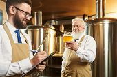 Two Brewers Standing In Brewery And Examining Quality Of Ale. Bearded Man Keeping Glass Of Beer Whil poster