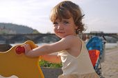 foto of lurch  - A playful little girl is rocking on the playground - JPG