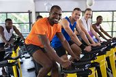 Portrait of diverse fit people exercising on exercise bike in fitness center. Bright modern gym with poster