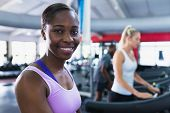 Close-up of African-american fit woman looking at camera while exercising on treadmill in fitness ce poster