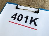 Paper With 401k Plan On Wood Table. poster